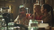Girls laugh, cheer and drink cocktails while having a good time together at a bar. video