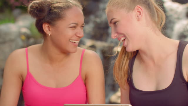 Girls laughing. Young women gossiping. Closeup of girlfriends read tablet video