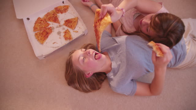 Girls lying on the floor sharing some take-away pizza video