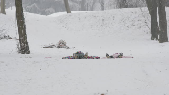 Girls making snow angels video
