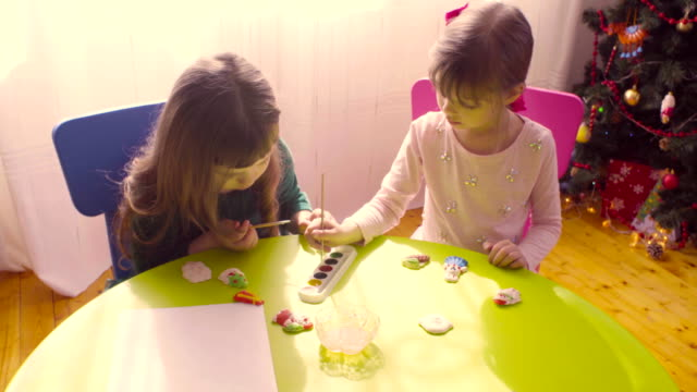 Girls near christmas tree painting ceramic toys video