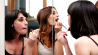 Girls night out  - friends apply makeup in a mirror video