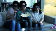 Girls on sofa watching Television with 3D glasses video