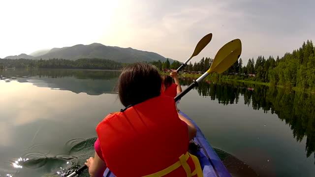 Girls paddling Kayak across a lake video