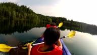 Girls paddling Kayak across a lake with pet dog video