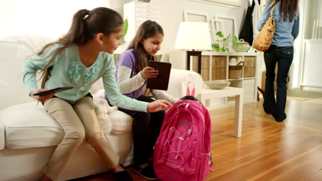 Girls play with tablet computers before school video