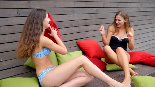 girls played colored Pillows on background Wooden wall, Slender young women in bathing suits resting video