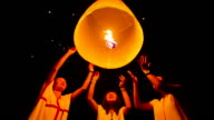 Girls release floating lanterns to the sky. video