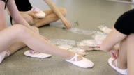 Girls sit on floor in dancing class elegantly stretching their legs video