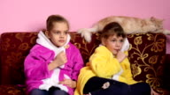 Girls sit on the sofa, lick lollipops and watch TV, the TV suddenly turned off video
