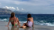Girls sitting on the shore during a storm. Big wave coming. video