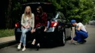 Girls sitting on trunk while mechanic fixes car video