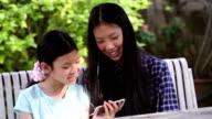 Girls watching cartoon or movie on smartphone video