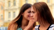 Girls whispering on a bench video