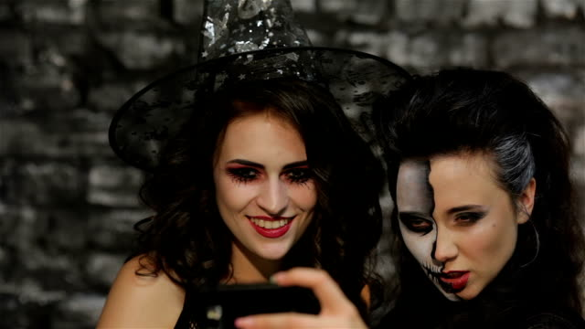 Girls-witch and skeleton make selfie video