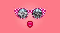 Glamorous sunglasses with hypnotic spirals and pink lips on changing colored backgrounds video