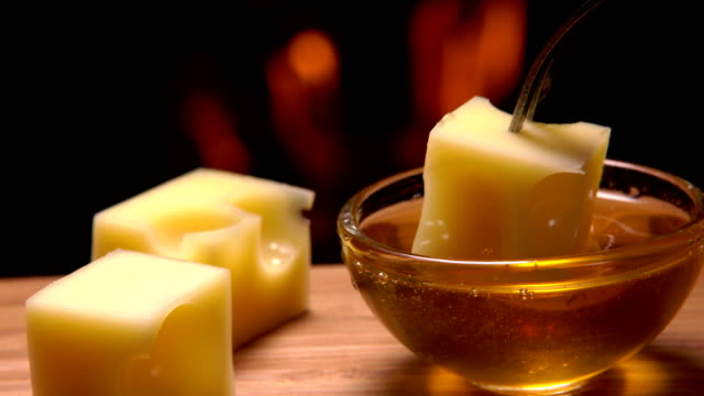 Glass bowl with honey and cheese on a background of a fireplace video