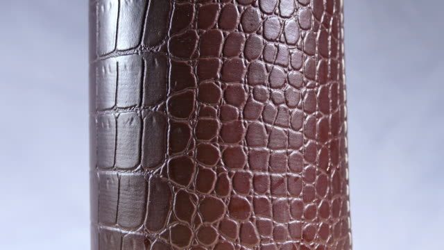 Glass cylinder made of crocodile leather. video
