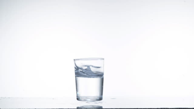 Glass Falling and Water splashing against White Background, Slow Motion 4K video