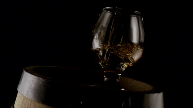 A glass for cognac is on a wooden barrel. Black background. Slow mo video