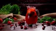 Glass jug of freshness strawberries lemonade. video