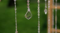 Glass long garlands hanging in forest on wedding day outdoors video