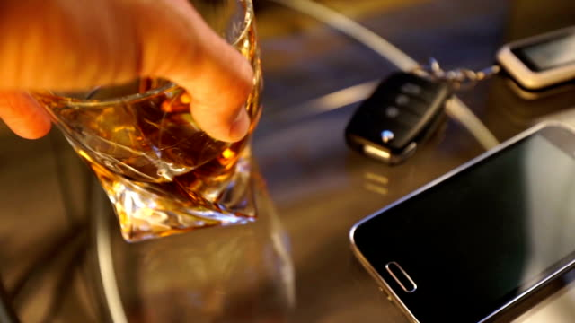 Glass of alcoholic drink and car key, on the table, light background video