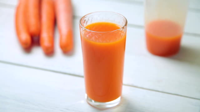 A glass of fresh carrot juice revolves around its axis on white wooden table video