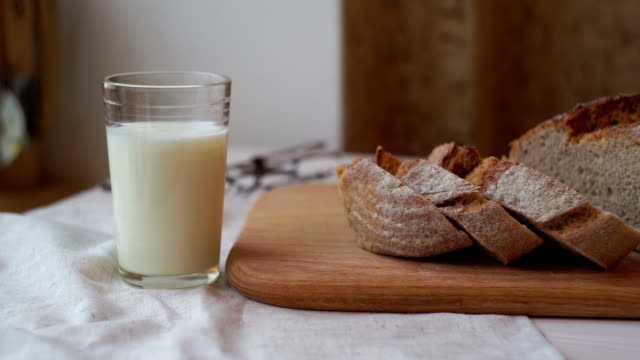 Glass of milk and bread slice on wooden board. Milk cup and sliced bread video