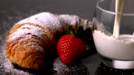 Glass of milk being poured next to strawberry and croissant video