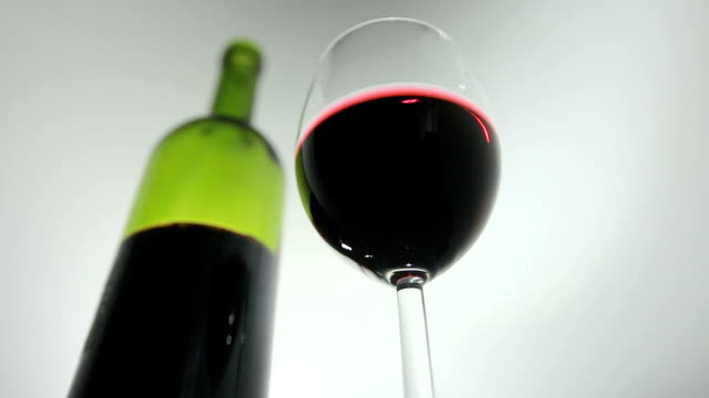 Glass of red wine and bottle on a background video