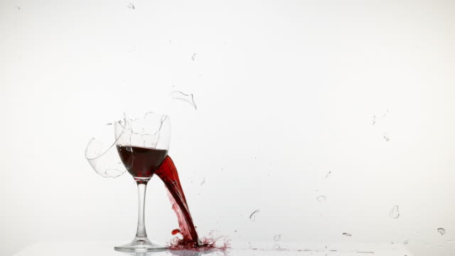 Glass of Red Wine Breaking and Splashing against White Background, Slow motion 4K video