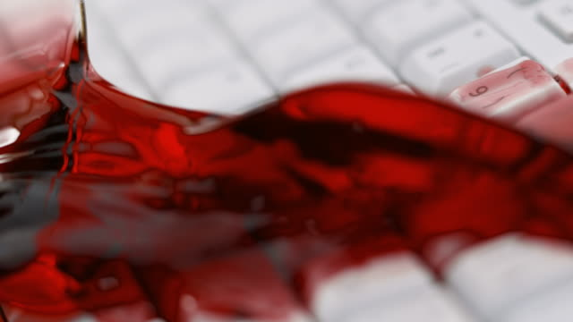 SLO MO LD Glass of red wine hitting a white keyboard and spilling wine on the keys video