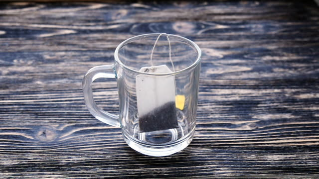 Glass of tea with teabag and pouring water in slowmotion video