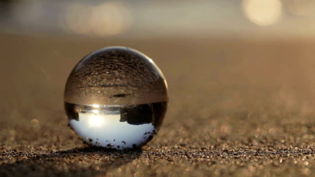 Glass sphere on a sandy beach video