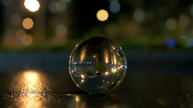 Glass sphere on the road in night city video