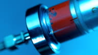 A glass syringe filling injection blood on a blue background. Macro video