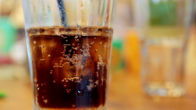 Glass with cola and ice on a table video