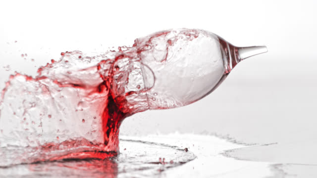 SLO MO of glass with red wine smashing on table video