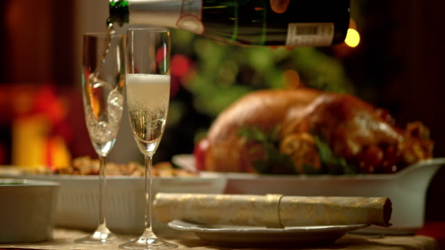 SLO MO glasses being poured with champagne at Christmas table video