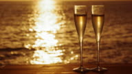 SLO MO Glasses of sparkling wine on beach at sunset video