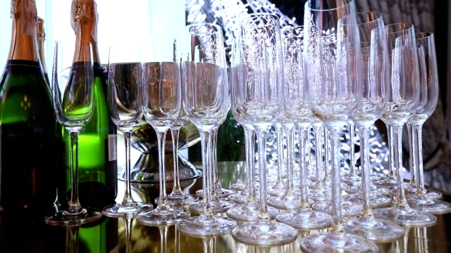 Glasses on the buffet table, a bottle of champagne, restaurant design, interior, indoors, smooth movement of the camera along the table, rows of wine glasses on the table, shallow depth of field video