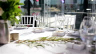 Glasses on white cloth table served for lunch or dinner in luxurious outdoor terrace restaurant with cozy interior video