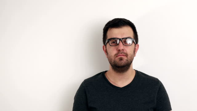 Glasses young man look at camera with white background video