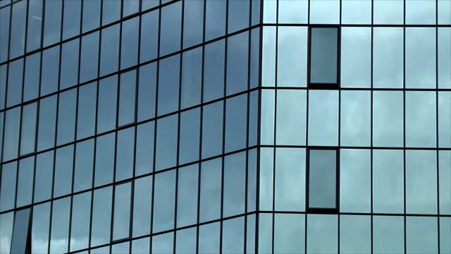 Gloomy clouds are reflected in the windows of the office building. Time lapse. video