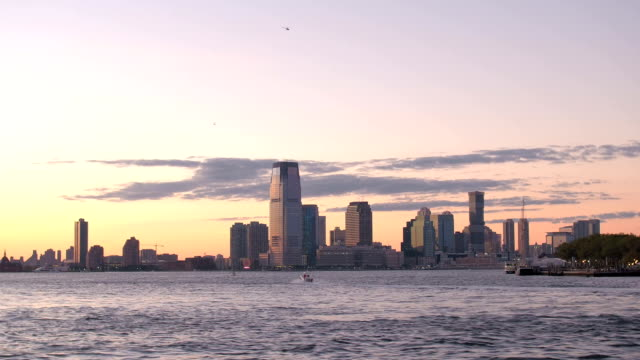 Glow of golden sunset on magical Jersey City skyline as seen from the East River video