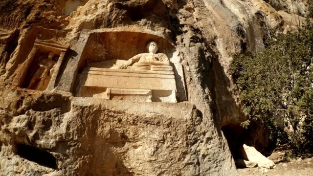 God lies with bowl in hand near little man figures in niches Adamkayalar Mersin province Turkey video