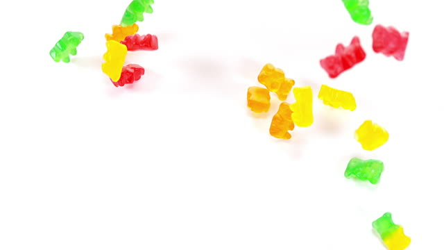 Gold Bears or Gummy Bears falling against White Background, Slow Motion video