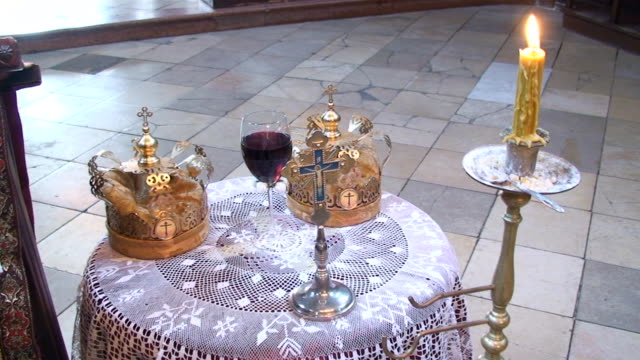Gold cross with crown and wine on a table video