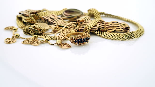 Gold jewelry turning slowly with copy space video
